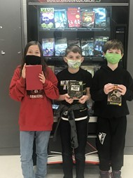 Caylin Nash, Preston Tabb, and Abban Stevens earn a book from the Hero Book Vending Machine.